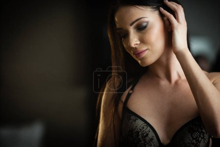 Photo for Beauty of woman body and lingerie concept. Beautiful brunette female fashion model in sexy black underwear poses in luxury hotel room. Young girl stands near a bed in bedroom wearing bra and panties. - Royalty Free Image