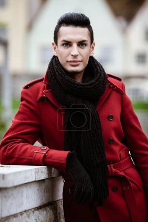 Photo for LGBTQ community lifestyle concept. Young homosexual man stands near stone fence. Handsome fashionable gay male model poses in cityscape outdoors. Wears red coat, gloves, and black scarf. - Royalty Free Image