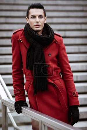 Photo for LGBTQ community lifestyle concept. Young homosexual man stands on a stairs. Handsome fashionable gay male model poses in cityscape outdoors. Wears red coat, gloves, and black scarf. - Royalty Free Image