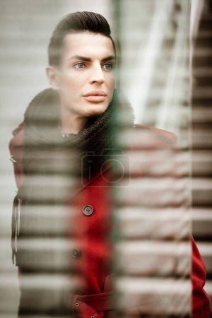 Photo pour Concept de style de vie communautaire LGBTQ. Jeune homme homosexuel se tient derrière le verre. Beau modèle masculin gay à la mode pose dans le paysage urbain en plein air. Porter un manteau rouge, des gants et une écharpe noire. - image libre de droit