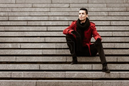 Photo for LGBTQ community lifestyle concept. Young homosexual man sits on a stairs. Handsome fashionable gay male model poses in cityscape outdoors. Wears red coat, gloves, and black scarf. - Royalty Free Image