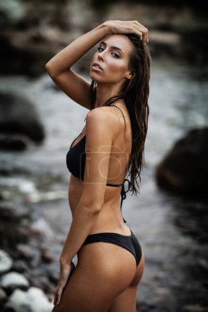Photo for Summertime recreation concept. Beautiful young sexy woman with fit trained slim body wearing black swimwear bikini walks on a beach. Fashion female model poses by the sea. - Royalty Free Image