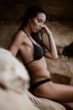 Photo for Summertime recreation concept. Beautiful young sexy woman with fit trained slim body wearing black swimwear bikini sits on a beach on a stone. Fashion female model poses by the sea. - Royalty Free Image