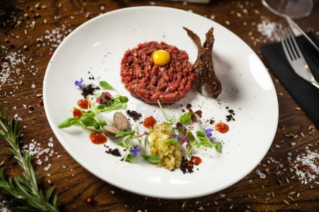 Photo for Steak tartare. Horseradish creme, black bread, baguette chips on white plate. Delicious healthy raw meat food closeup served on a table for lunch in modern cuisine gourmet restaurant - Royalty Free Image