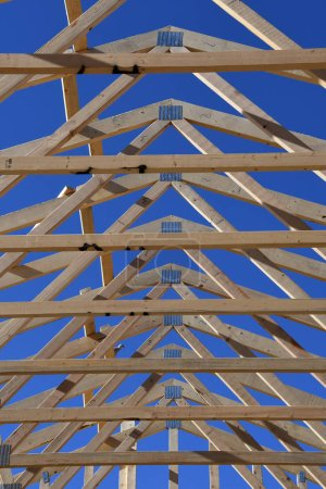 New home under construction with wood, trusses and supplies against blue sky in the Southwest part of the United States in Gilbert Arizona.