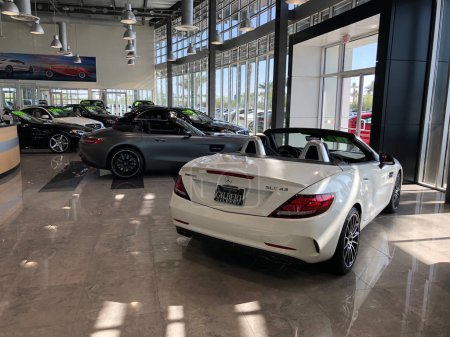 Mercedes-Benz car dealership with cars on display in a showroom in Gilbert Arizona in the Southwest part of the United States. Mercedes-Benz is a global automobile marque and a division of the German company Daimler AG.
