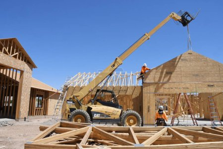 Photo for New construction framing being assembled by a crew from the construction company that the workers are employed by. These houses being built in Arizona which is in the Southwest part of the United States. - Royalty Free Image