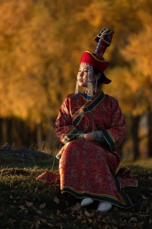 Photo for Beautiful young woman posing in traditional Mongolian dress in sunset light. Ulaanbaatar, Mongolia. - Royalty Free Image