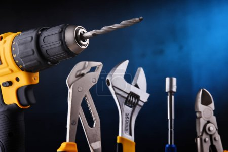 Photo for Composition with hardware tools including cordless drill and monkey spanner - Royalty Free Image