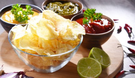 Photo for Composition with glass bowl of potato chips and dipping sauces. - Royalty Free Image