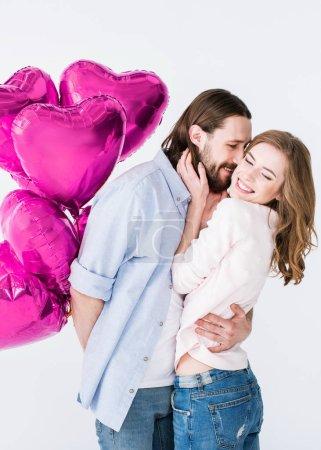 Photo pour Beau jeune homme tenant coeur en forme de ballons et embrassant sa petite amie, isolé sur blanc - image libre de droit