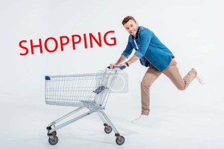 Happy young man running with shopping trolley and smiling at camera on grey, shopping inscription