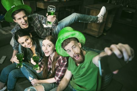 high angle view of group of happy friends with beer making selfie on St.Patrick's day