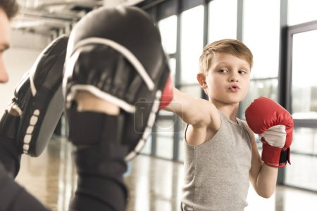 little boxer kid practicing punches with coach at gym