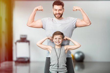happy little kid with his father showing muscles at camera