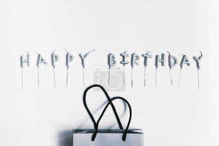 Esprit de sac et bougies papier lettres joyeux anniversaire sur fond gris. Flatlay, vue de dessus. Concept de fête et anniversaire