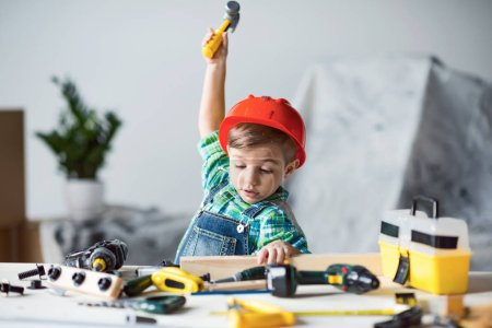 adorable little kid in red hard hat playing with wooden plank and toy hammer