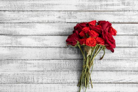 Photo for Top view of beautiful red roses bouquet on grungy grey wooden table with copy space - Royalty Free Image