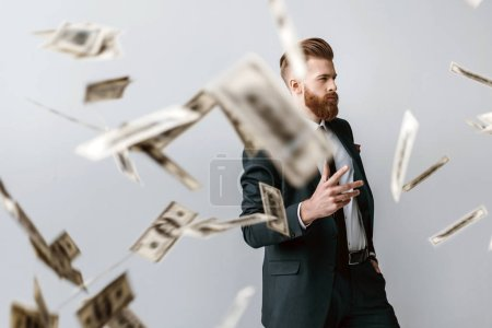 handsome elegant businessman with falling dollar banknotes on foreground isolated on grey