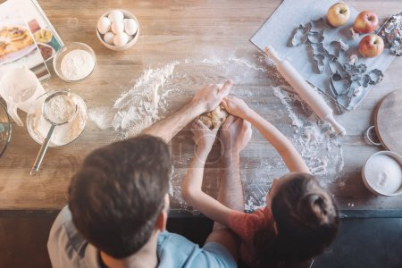 Overhead view of father and daughter kneading dough together