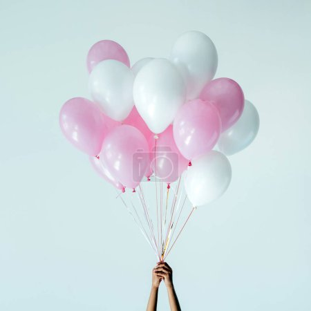 Photo for Cropped shot of hands holding bunch of pink and white balloons isolated on grey - Royalty Free Image