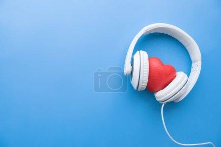 Photo pour Vue de dessus des écouteurs filaires avec signe cardiaque rouge au milieu sur la surface bleue - image libre de droit