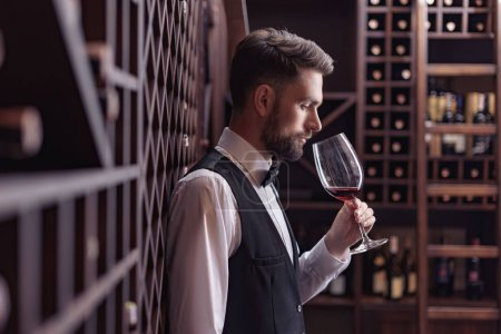 side view of young handsome sommelier tasting red wine in wine cellar while leaning on shelves