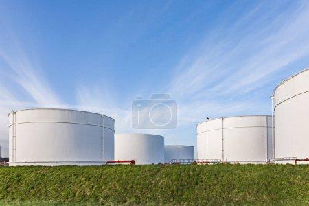 Photo pour Réservoirs blancs pour l'essence et l'huile dans le parc de réservoirs avec ciel bleu - image libre de droit