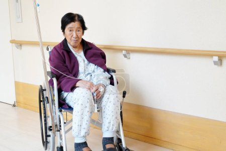 Photo pour Femme âgée ou âgée assise en fauteuil roulant dans le couloir de l'hôpital - image libre de droit