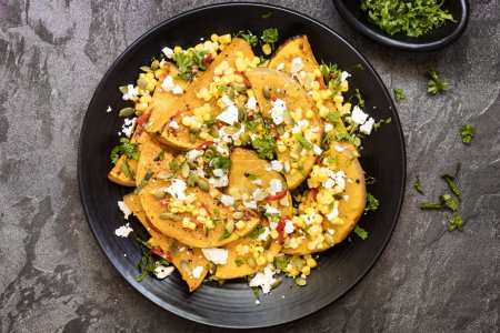Photo for Roasted butternut squash or pumpkin with a sweetcorn and chili sasa, feta cheese and pepitas.  With fresh mint.  Top view on slate. - Royalty Free Image