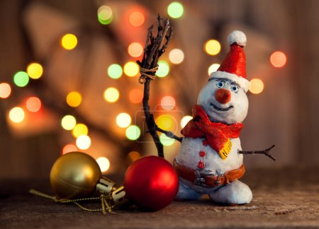 Photo for Funny Christmas snowman, garland and toys on wooden table - Royalty Free Image