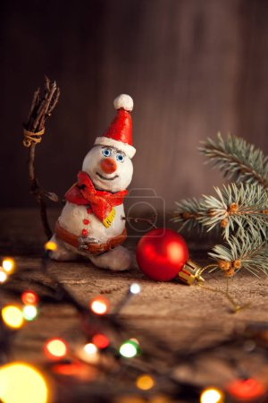 Christmas snowman, fir tree, garland and bauble on wooden table