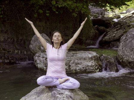 Photo pour Femme pratique le yoga dans la pose de lotus au lac de montagne - image libre de droit
