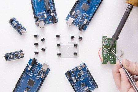 Photo pour Six planches pour la robotique, l'impression 3D ou les développements et inventions. Une main d'homme avec un fer à souder. Vous pouvez voir la fumée de colophane. Tableaux d'apprentissage en Fablab - Nano, Uno et Mega - image libre de droit