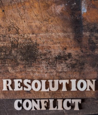'RESOLUTION' and 'CONFLICT' text on wooden background.