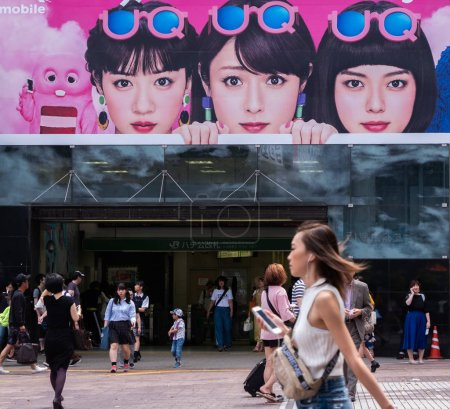TOKYO, JAPAN - JULY 1ST, 2018. People walkingat  Hachiko square, Shibuya with a huge advertisement in the background.