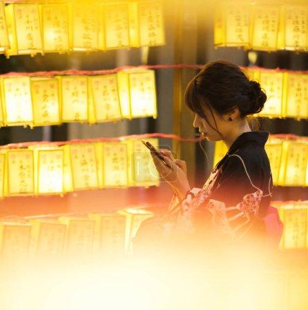 Foto de TOKIO, JAPÓN - 14 DE JULIO DE 2018. Chica japonesa en vestido tradicional yukata entre las linternas amarillas en el santuario de Yasukuni durante Mitama (o Soul) Festival de Verano . - Imagen libre de derechos