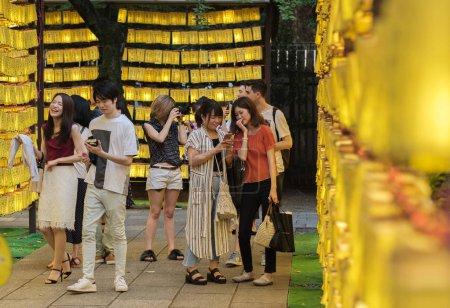 Foto de TOKIO, JAPÓN - 14 DE JULIO DE 2018. Visitantes y turistas caminando entre las filas de faroles de papel amarillo en el Santuario de Yasukuni durante el Festival de Verano de Mitama (o Soul) . - Imagen libre de derechos
