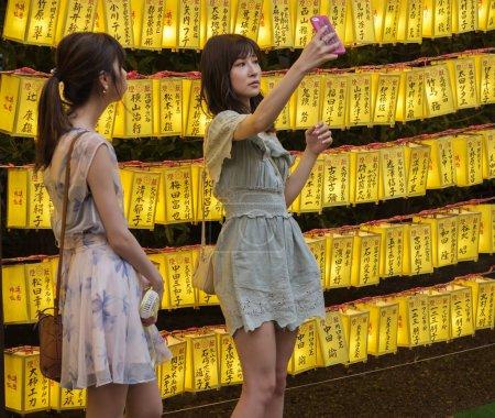 Foto de TOKIO, JAPÓN - 14 DE JULIO DE 2018. Chicas japonesas con smartphone entre las linternas amarillas en el Santuario de Yasukuni durante el Festival de Verano Mitama (o Soul) . - Imagen libre de derechos