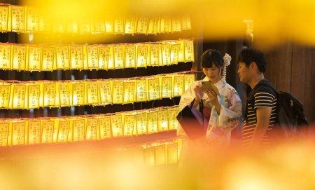 Foto de TOKIO, JAPÓN - 14 DE JULIO DE 2018. Pareja japonesa entre las linternas amarillas en el Santuario Yasukuni durante el Festival de Verano de Mitama (o Soul) . - Imagen libre de derechos