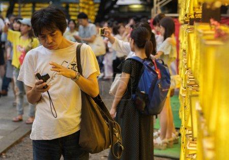 Foto de TOKIO, JAPÓN - 14 DE JULIO DE 2018. Visitantes con smartphone entre las linternas amarillas del Santuario de Yasukuni durante el Festival de Verano de Mitama (o Soul) . - Imagen libre de derechos