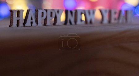 Feliz año nuevo Letras de madera con fondo de luces bokeh. Enfoque selectivo