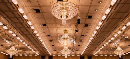 Photo pour Énorme lustre éclairé suspendu au plafond . - image libre de droit