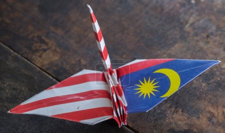 Malaysian flag origami paper crane on wooden table top