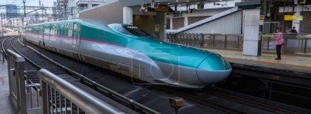 TOKYO, JAPAN - AUGUST 17TH, 2018.   High speed bullet train arriving  at Tokyo Railway Station platform.