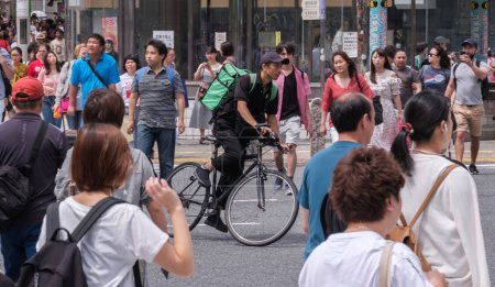 TOKYO, JAPAN - AUGUST 19TH, 2018. Uber Eats rider cycling through the street of Shibuya.