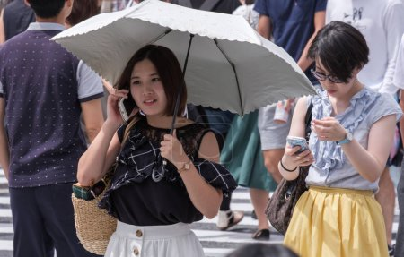 TOKYO, JAPAN - AUGUST 19TH, 2018. Japanese girl with smartphone and umbrella waiting to cross the street in Shibuya.