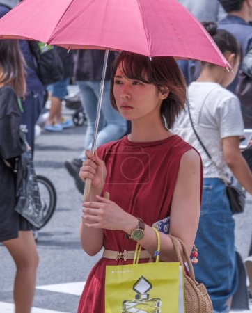 TOKYO, JAPAN - AUGUST 19TH, 2018.  Japanese woman with red umbrella and dress during a hot summer day in Shibuya.