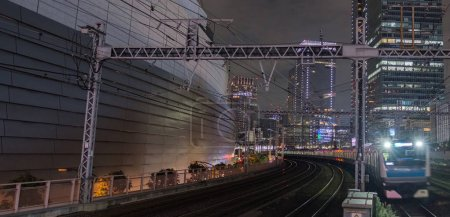 TOKYO, JAPAN - SEPTEMBER 15TH, 2018. Blurred motion of East Japan Railway Keihin Tohoku line passing thorugh Yurakucho Station tracks at night..