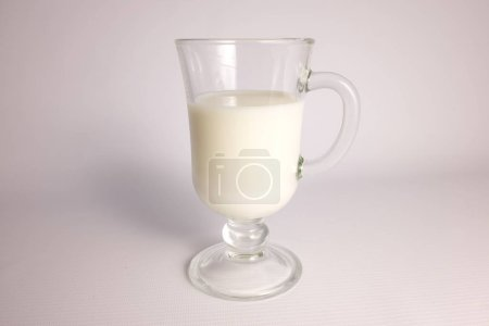Glass of milk in transparent glass on white background
